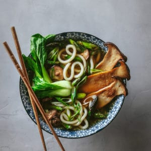 bowl of vegetable udon noodle soup with chopsticks set on top