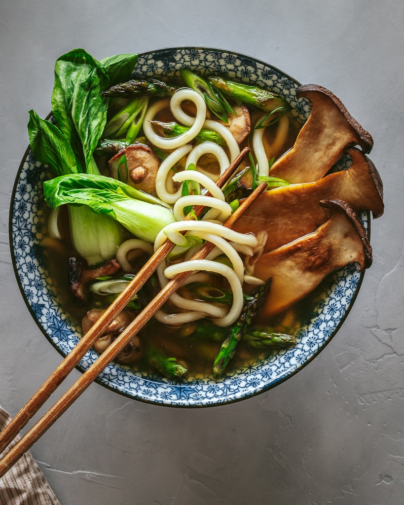 bowl of vegetable udon noodle soup with chopsticks twirling noodles