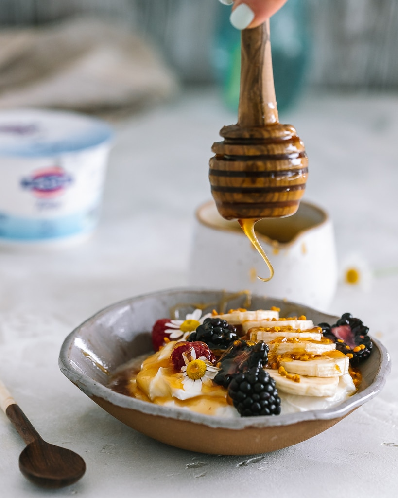 honey being drizzled into a yogurt bowl with sliced bananas and berries