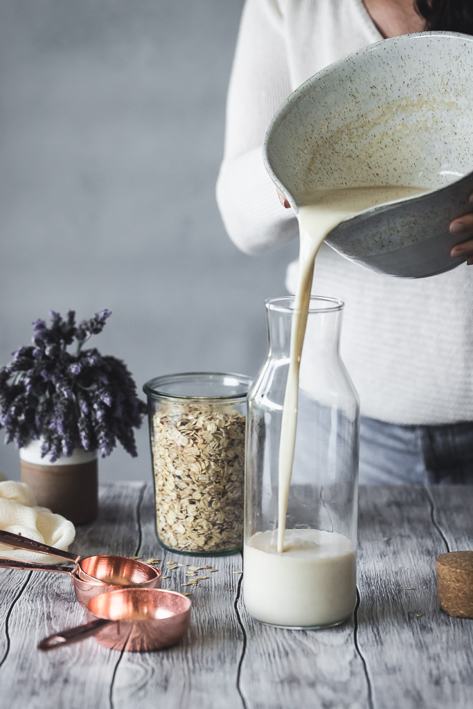 oat milk being poured into a carafe