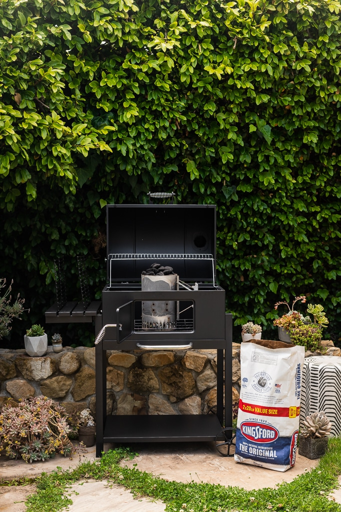 A charcoal grill and a bag of charcoal briquettes set against a backdrop of green shrubs and surrounded by potted succulents