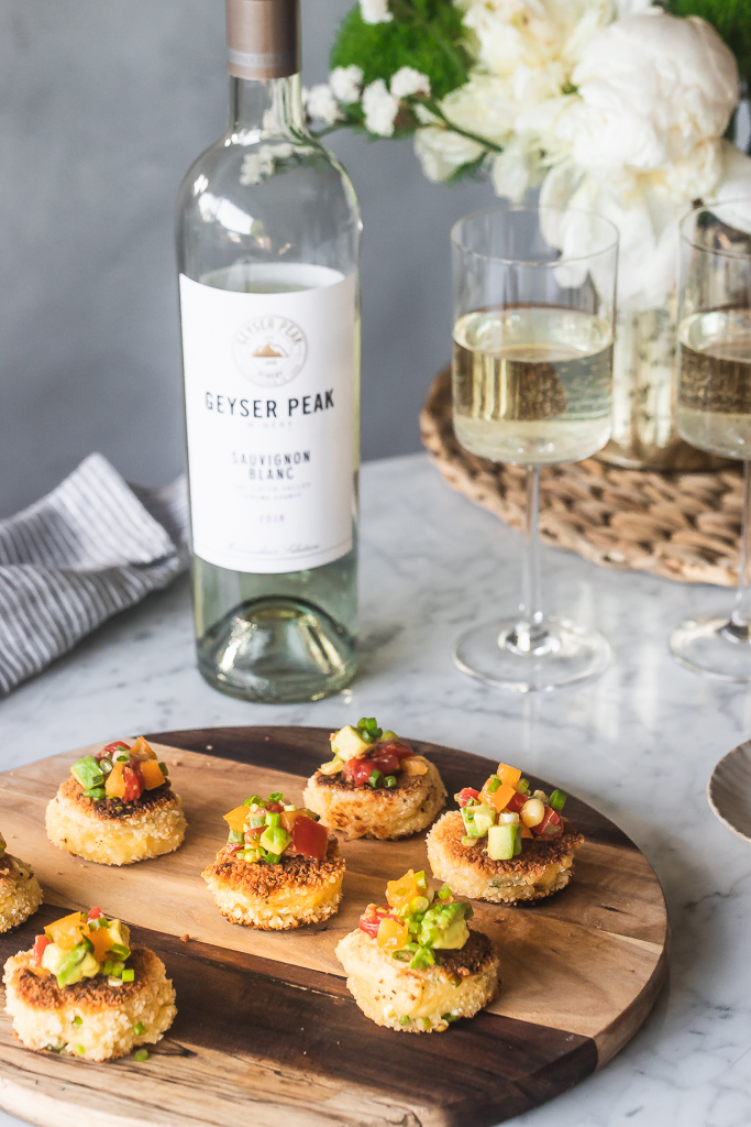 corn fritters on a wooden cutting board with glasses of white wine