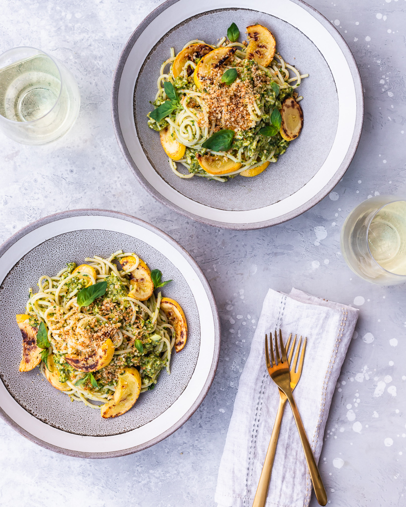 Two bowls of spaghetti with green olive pesto and yellow squash