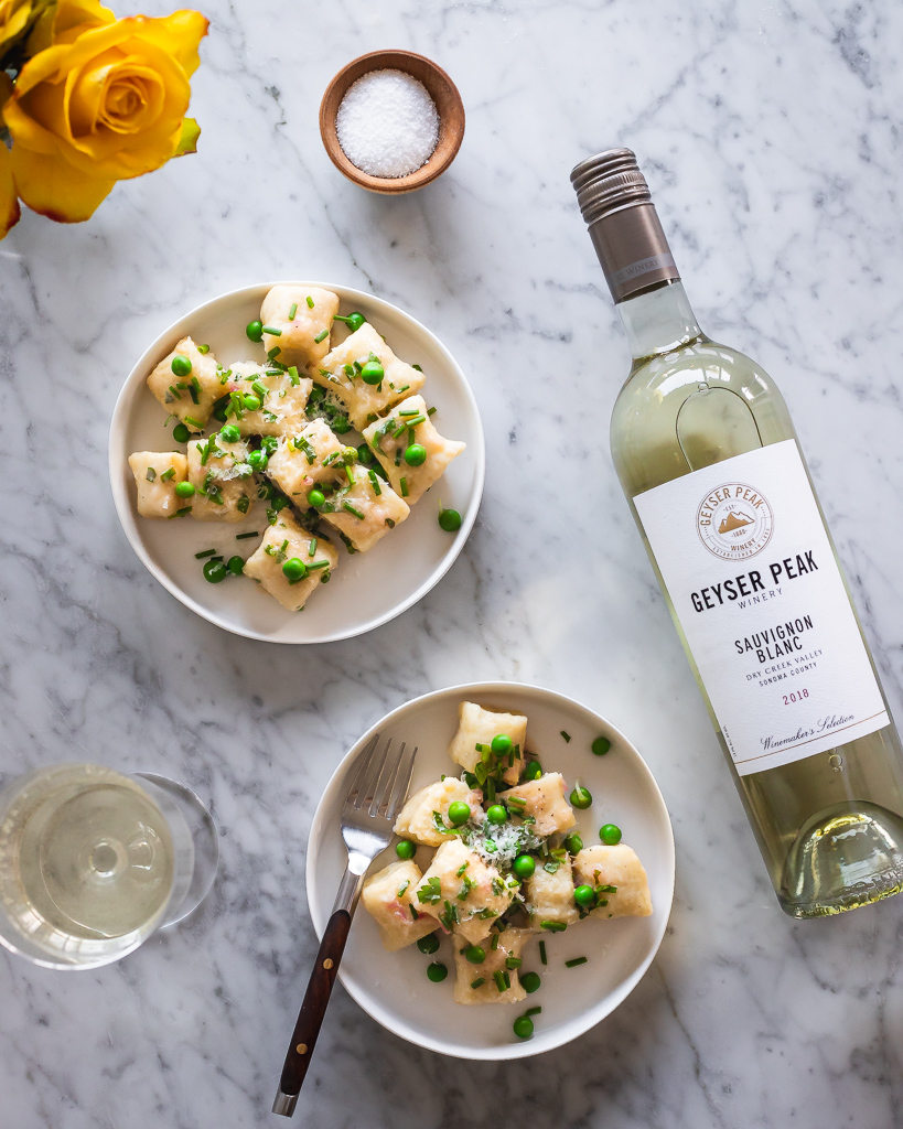 plates of pea gnocchi next to a white wine bottle