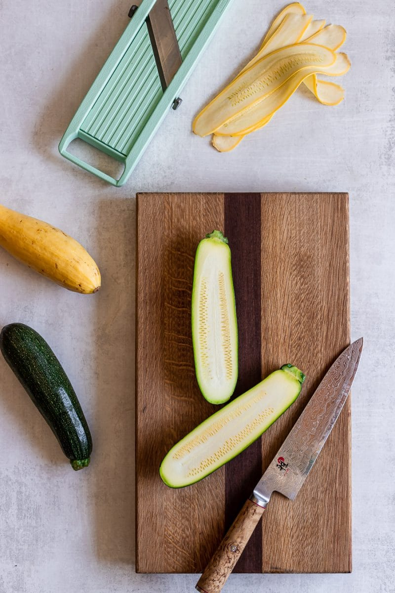 a mandolin and shaved zucchini ribbons on a cutting board
