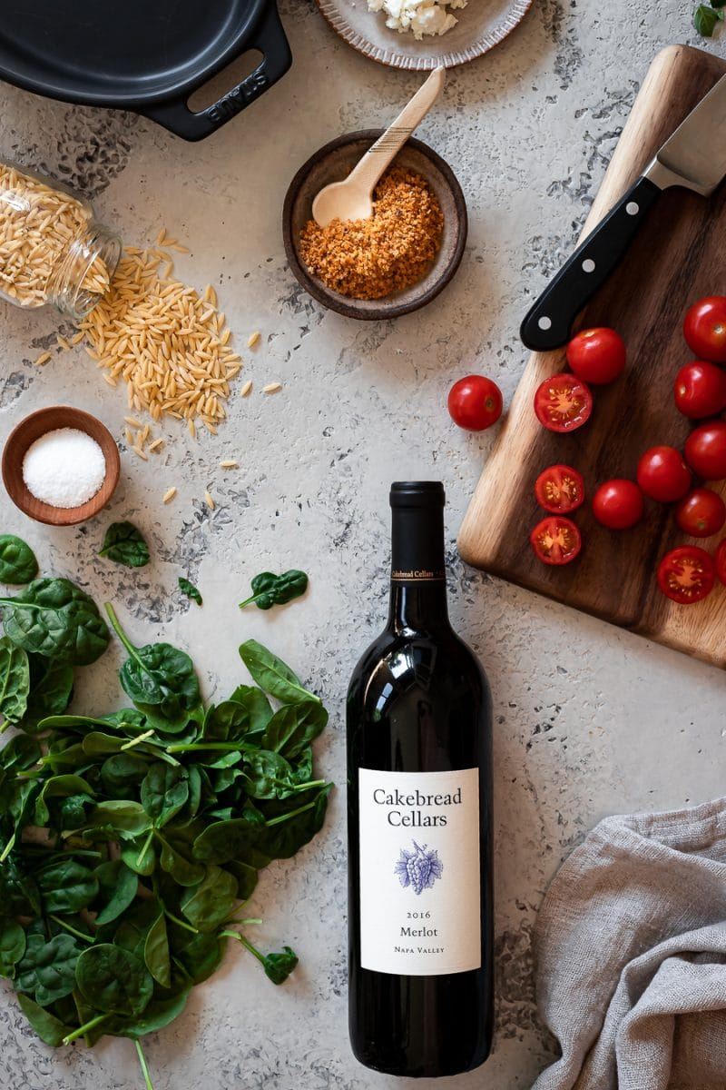 Ingredients including pasta, spinach, cherry tomatoes, feta, bread crumbs and red wine