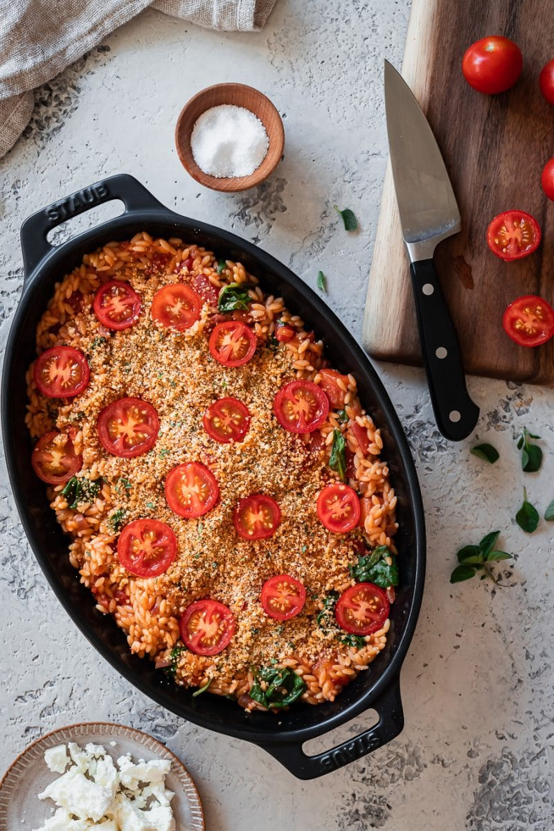 orzo topped with seasoned breadcrumbs and cherry tomato halves in a baking dish