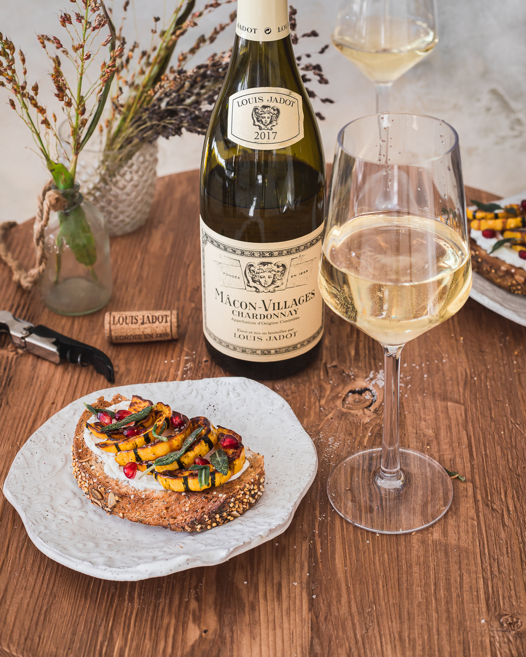 roasted delicata squash and goat cheese tartine on a white Porcelaine plate with a glass of chardonnay on the side