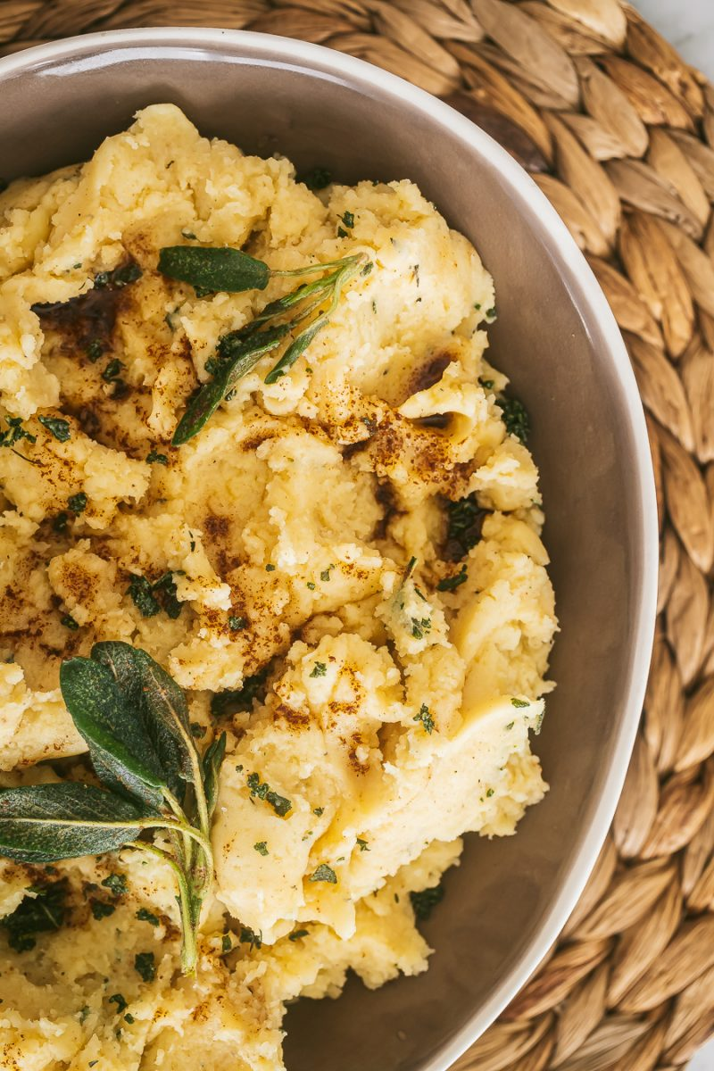 a bowl of mashed potatoes topped with browned butter, crispy sage and thyme