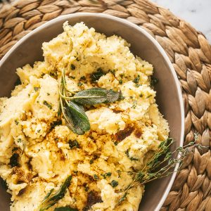 browned butter herb mashed potatoes in a taupe colored ceramic bowl