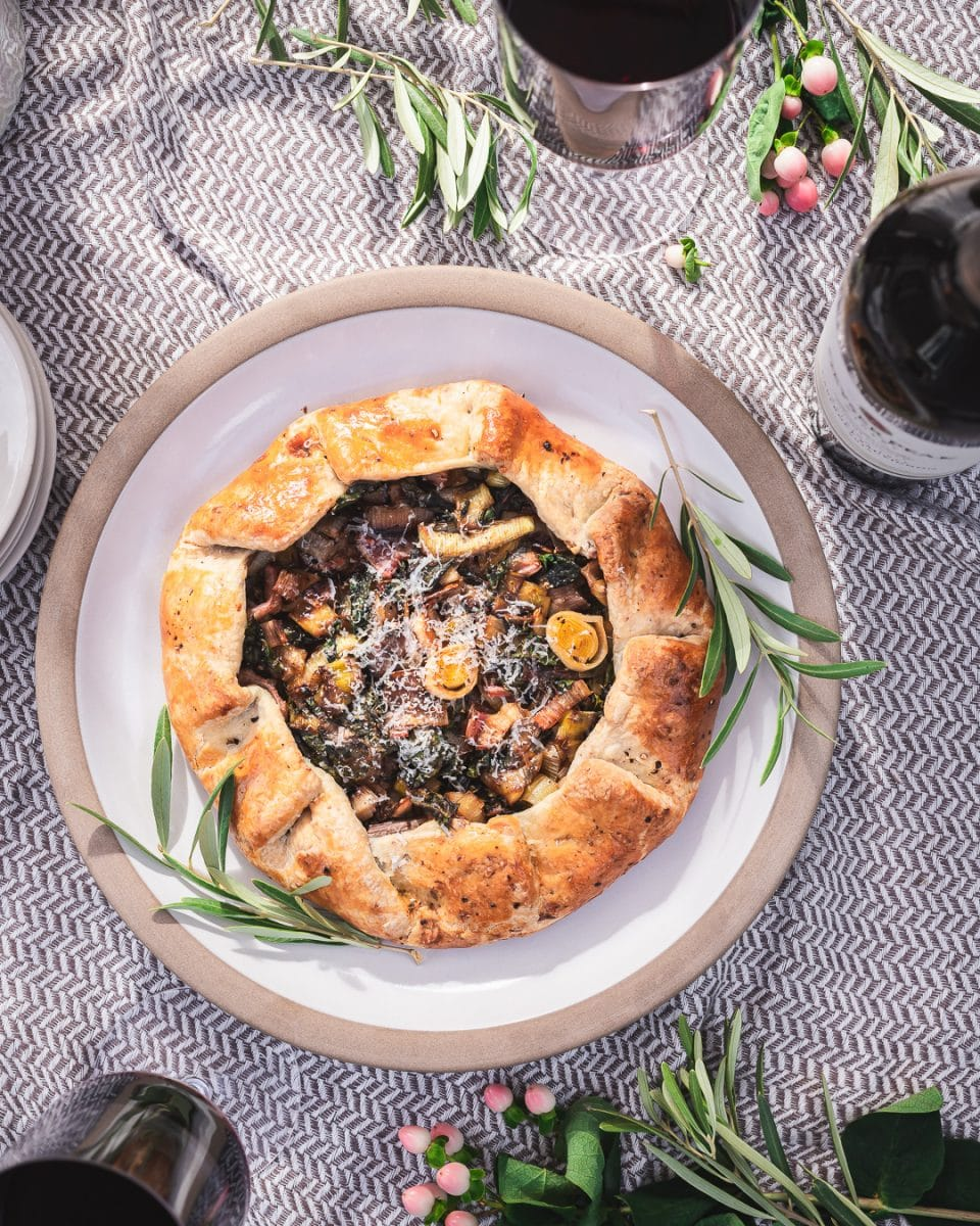 Leek and Swiss Chard Galette on a plate with olive leaf garnish