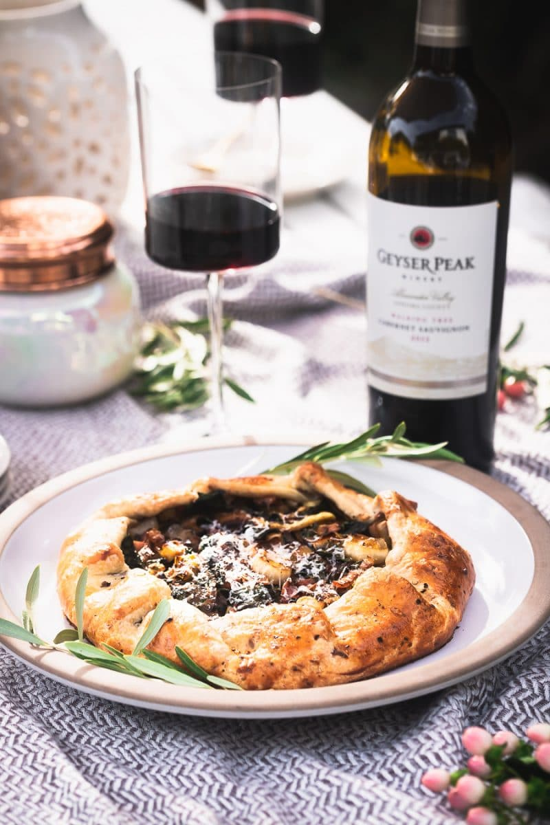 A leek and swiss chard galette at an outdoor table with a bottle of red wine