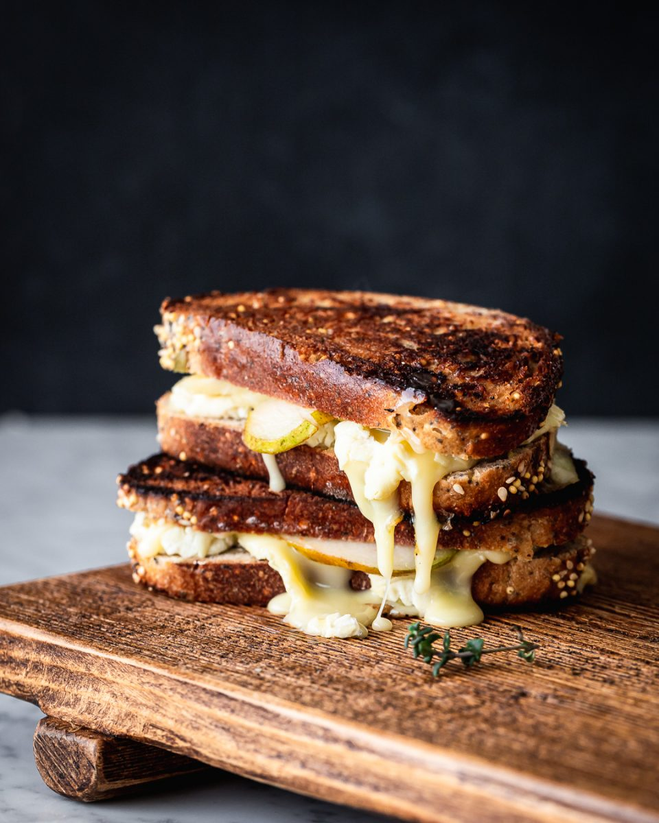 Two brie and pear grilled cheese sandwiches stacked on top of one another on a wooden board