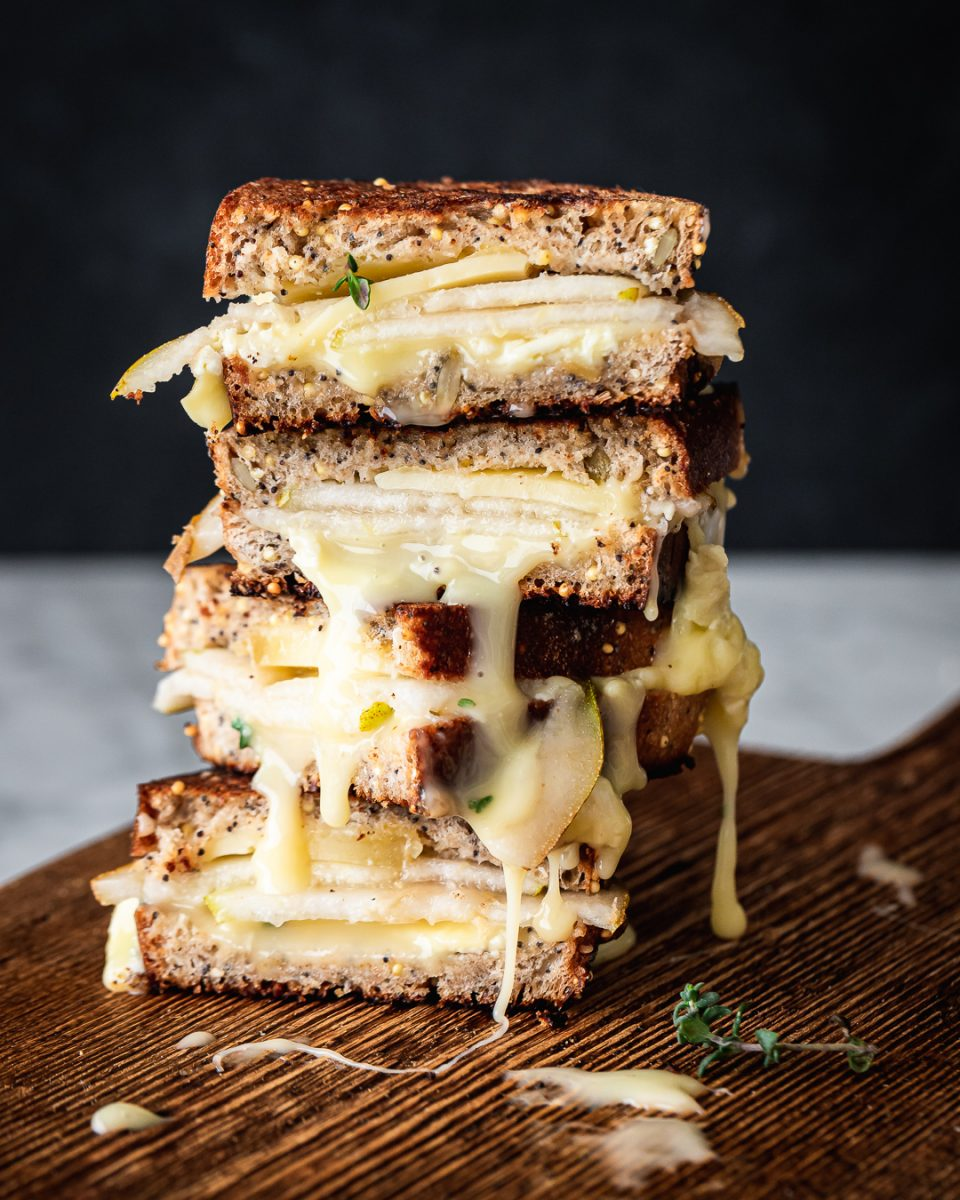 Four stacked slices of a grilled cheese sandwich with pear and melted brie on a wood serving board