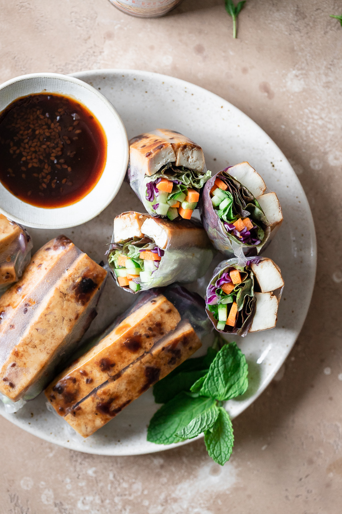 tofu spring rolls sliced in half on a plate with teriyaki dipping sauce