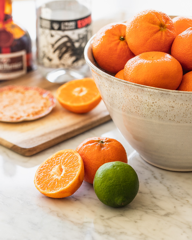 a ceramic bowl filled with clementines with a bottle of mezcal
