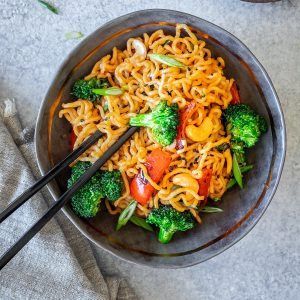 A bowl of ramen stir fry with broccoli and bell pepper