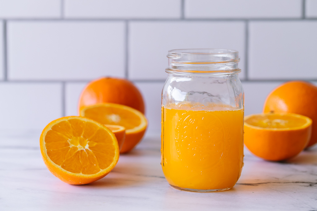 a mason jar filled with freshly squeezed navel oranges