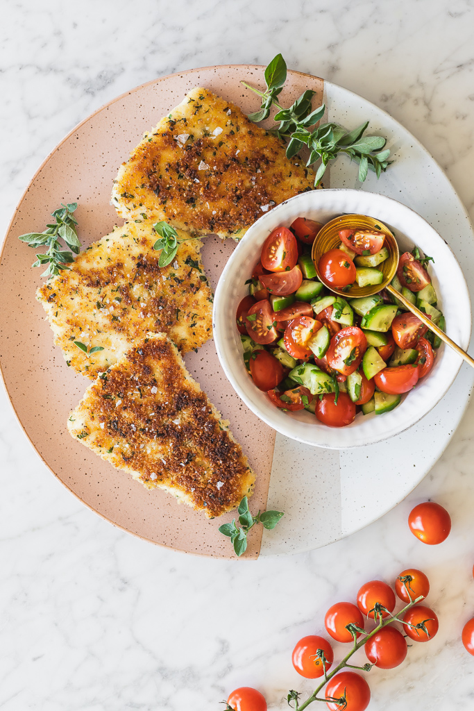 overhead shot of a palte with three pieces of panko crusted halibut filets with a small bowl of cucumber tomato salsa