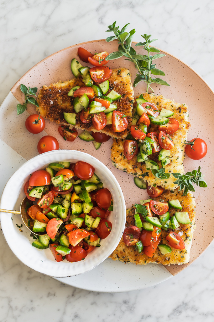 overhead shot of panko crusted halibut filets topped with tomato cucumber salsa