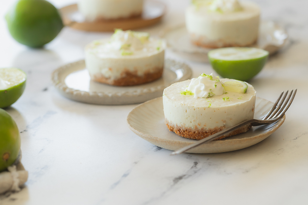 side view of four mini vegan margarita cheesecakes served on saucers
