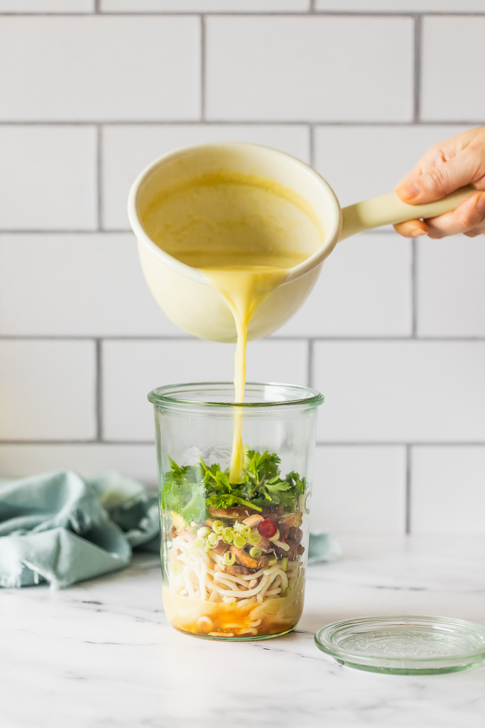 pouring coconut broth into a jar with soup ingredients