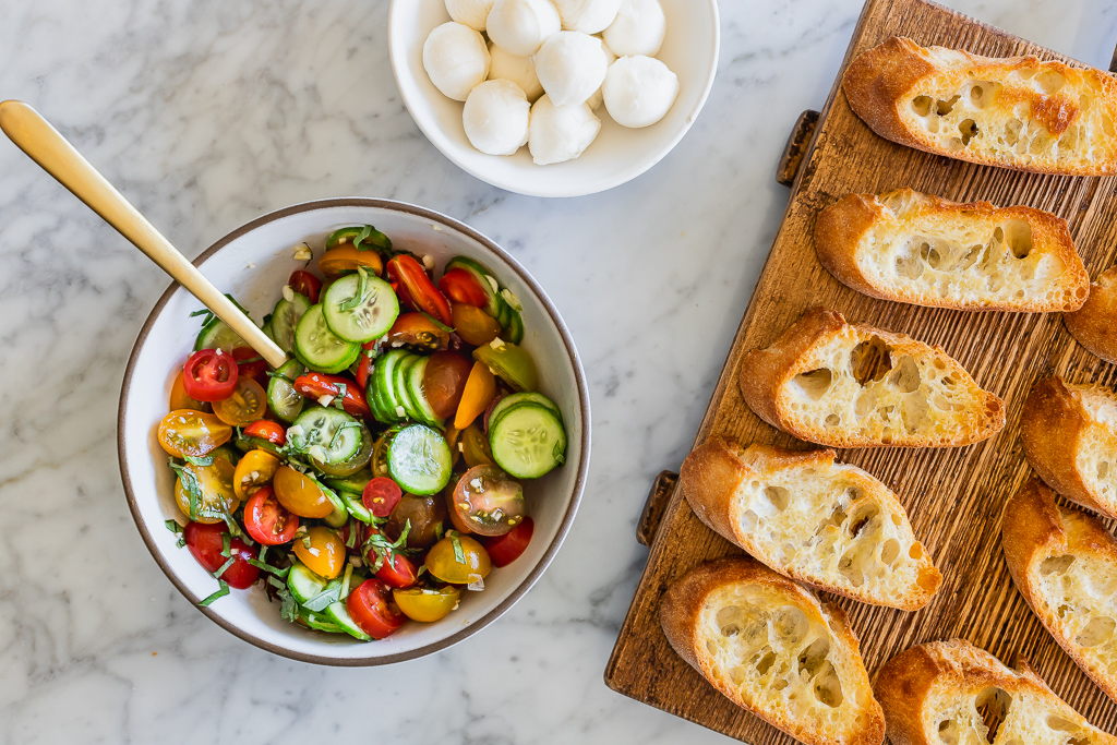 Cucumber, cherry tomatoes and basil in a bowl with toasted baguette slices and fresh mozzarella on a marble counter