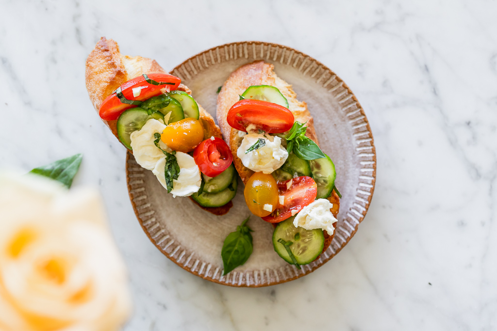 2 pieces of tomato and cucumber crostini on a ceramic appetizer plate