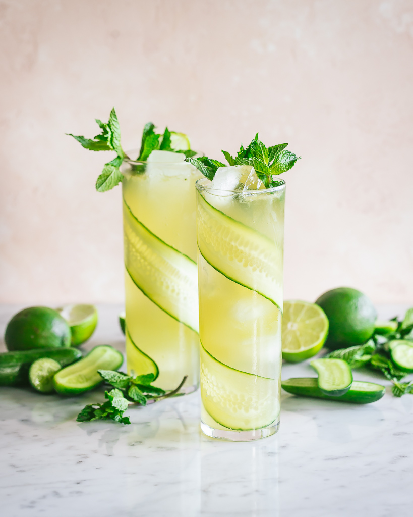 two cucumber mojitos in tall glasses with mint sprigs