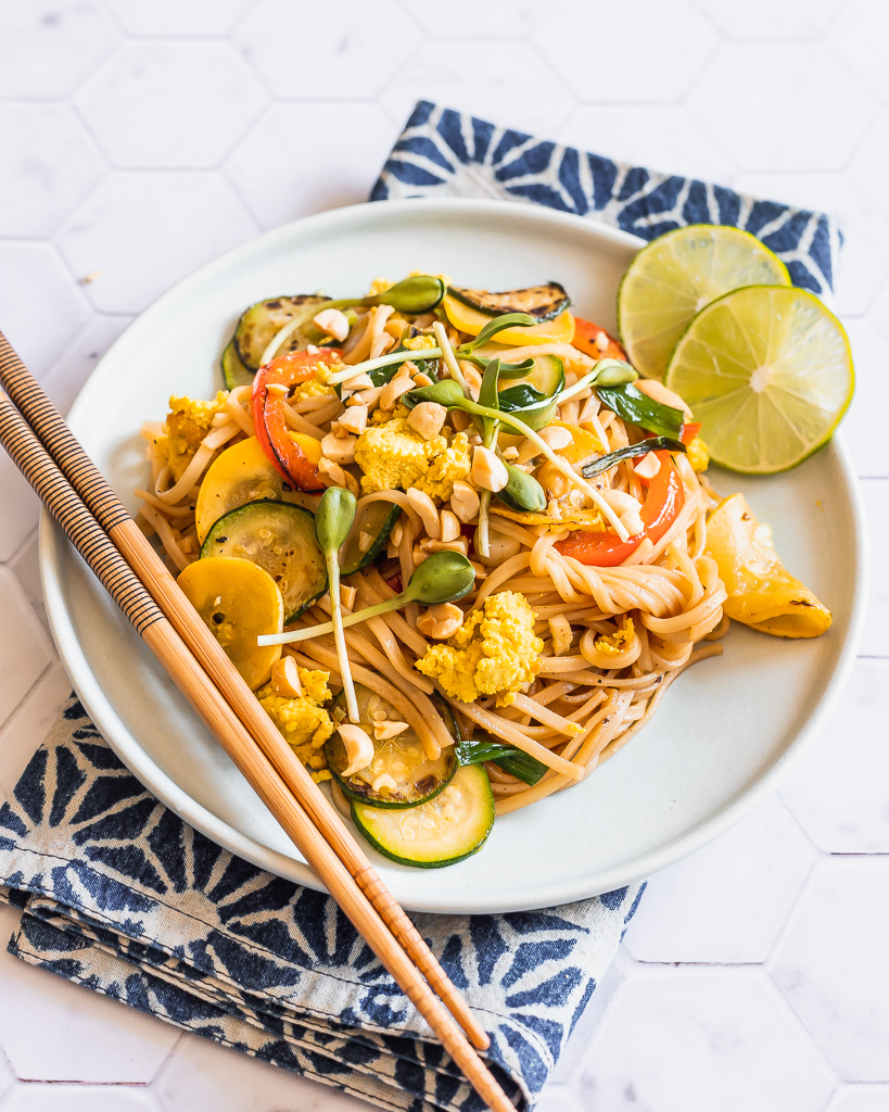 overhead shot of a plate with vegan pad thai with squash and lime slices on the side