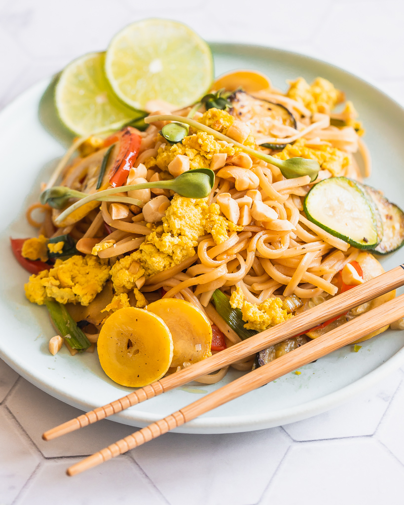 side view of a plate with easy vegan pad Thai with tofu scrambled eggs and squash with chopsticks on the side