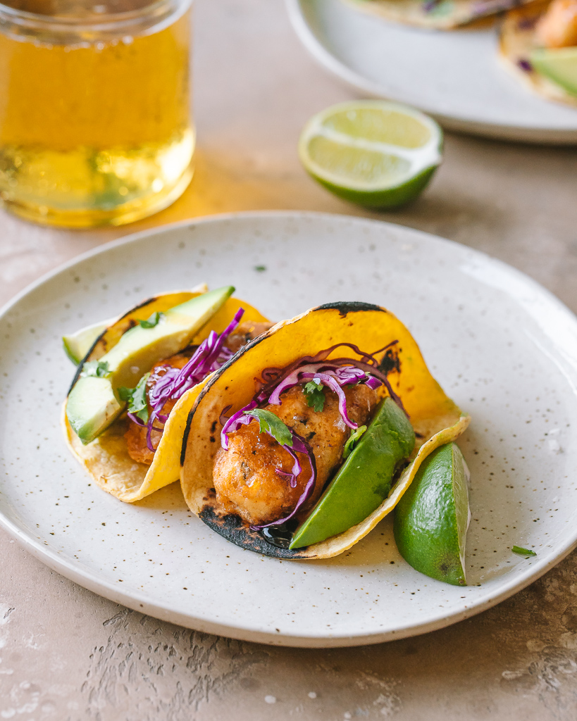 two healthy vegan beer battered fish tacos on a ceramic plate