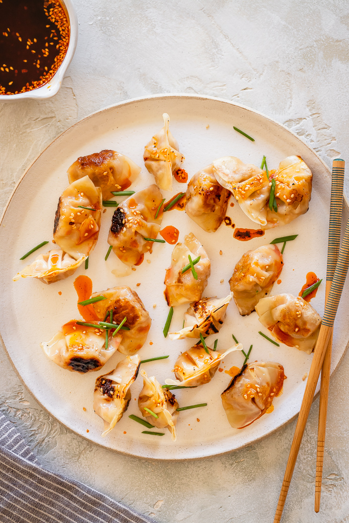 mini wontons and chives on a ceramic plate drizzled with chili oil
