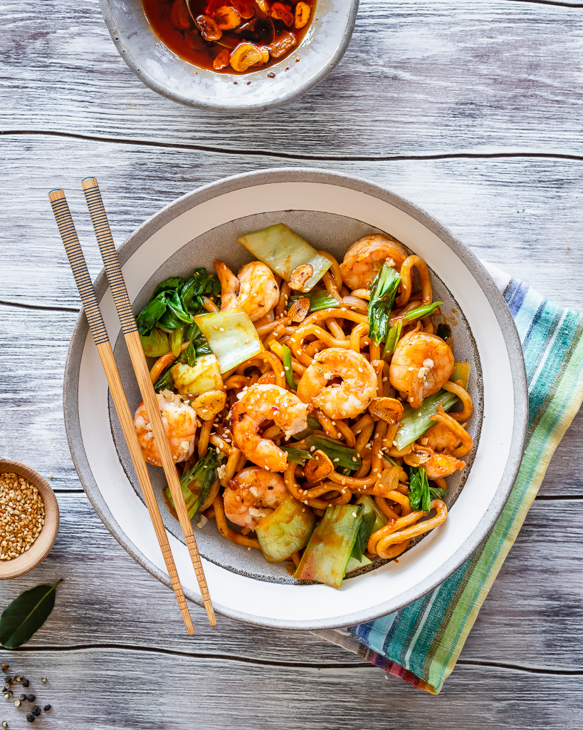 szechuan noodle bowl with homemade garlic chili oil and served with garlic shrimp on top