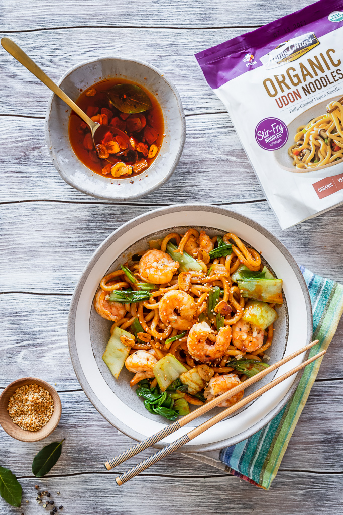 a szechuan noodle bowl with shrimp next to a small dish with homemade garlic chili oil