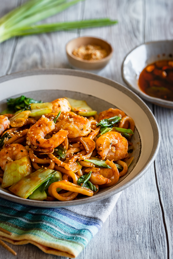 side view of szechuan noodle bowl with Asian greens and homemade garlic chili oil with garlic shrimp on top