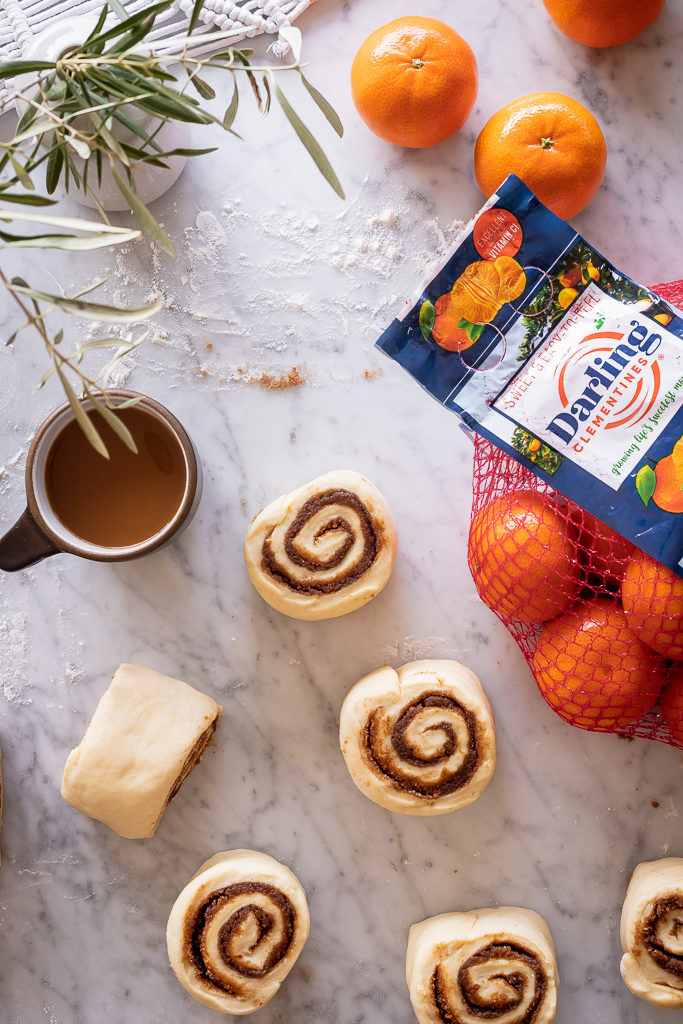 sweet roll dough cut into rolls with a bag of clementines