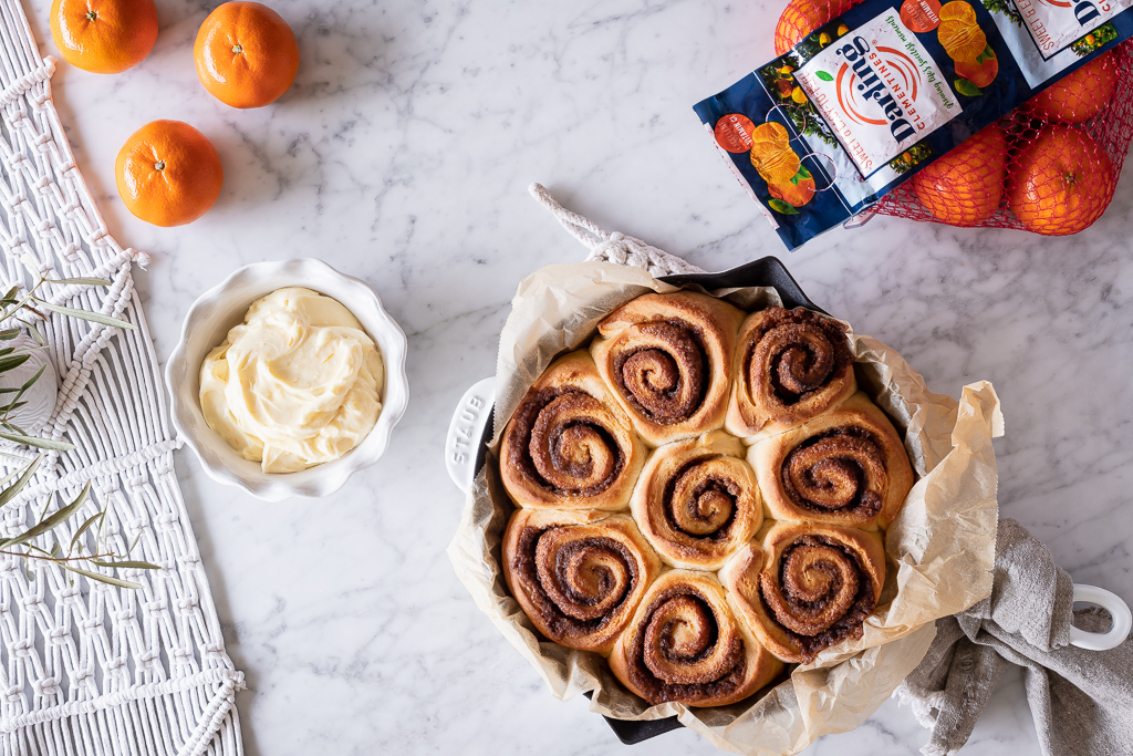 baked citrus sweet rolls, clementines and a bowl of cream cheese frosting