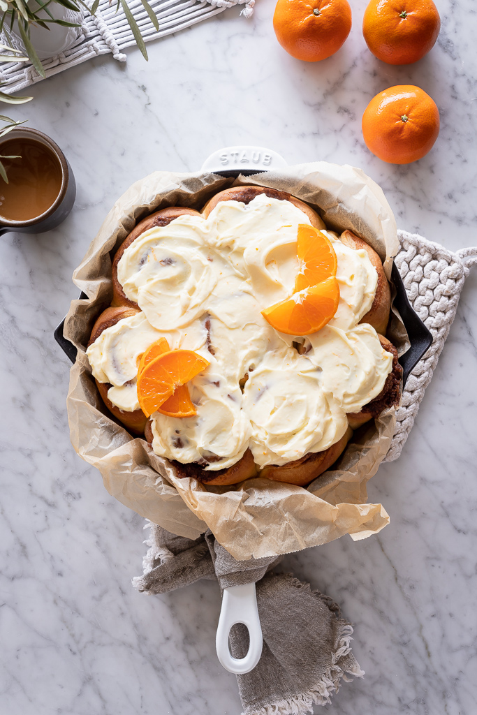 a cast iron skillet filled with citrus sweet rolls on a marble surface