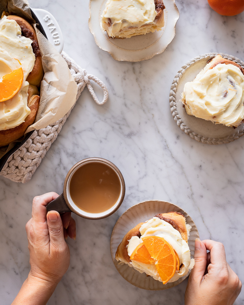 hands holding a cup of coffee and a plate with a citrus sweet roll