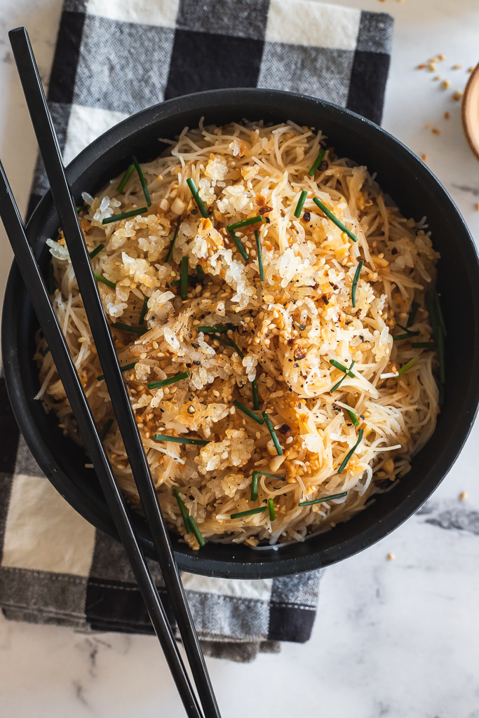 sesame garlic noodles topped with crispy rice and sesame seeds in a black bowl