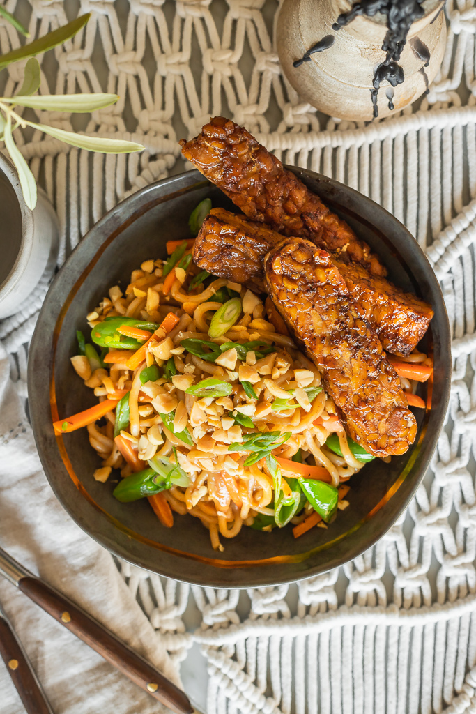 vegan thai peanut noodles with chopped peanuts, carrots, snap peas and tempeh
