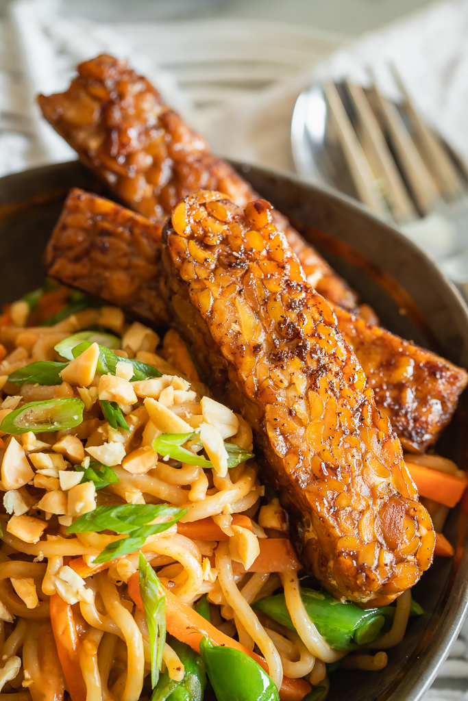 soy glazed tempeh served on a bed of vegan Thai peanut noodles