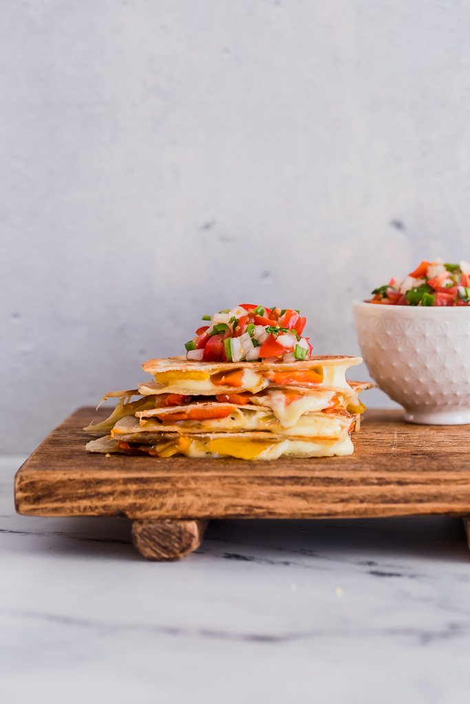a stack of quartered quesadillas with cheese oozing out of each piece