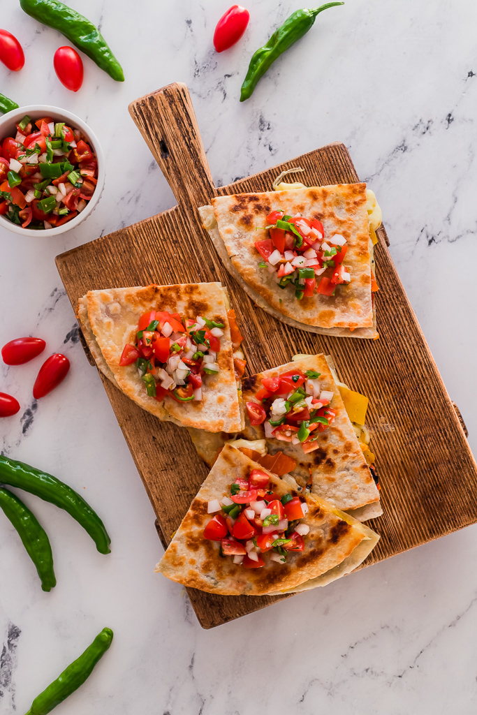 homemade vegetarian roasted bell pepper quesadillas cut into quarters and topped with shishito pepper salsa