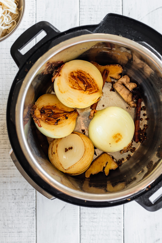 an instant pot with onions, ginger and other aromatics for pho