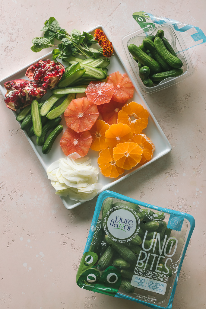 sliced cucumber, grapefruit and mandarin oranges on a rectangular ceramic platter; containers of nano cucumbers from Pure Flavor