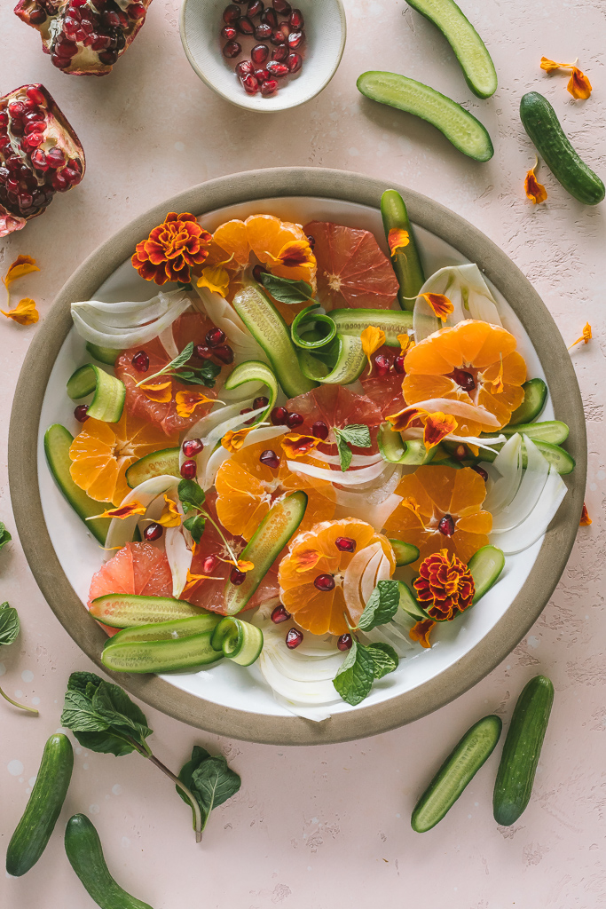 A citrus salad with shaved cucumber and fennel on a brown rimmed ceramic plate