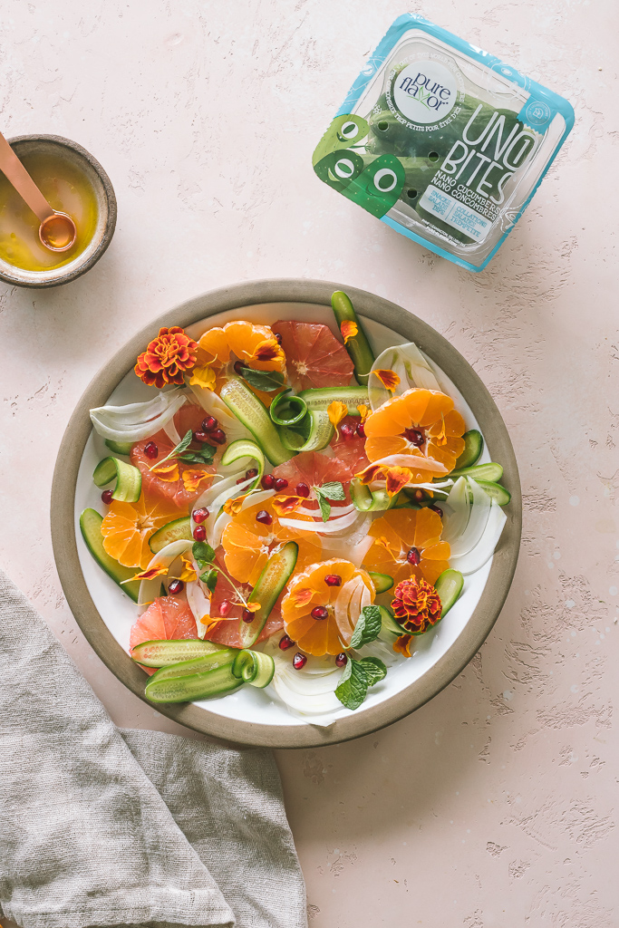 A citrus salad with shaved cucumber and fennel on a brown rimmed ceramic plate with a bowl of grapefruit vinaigrette on the side