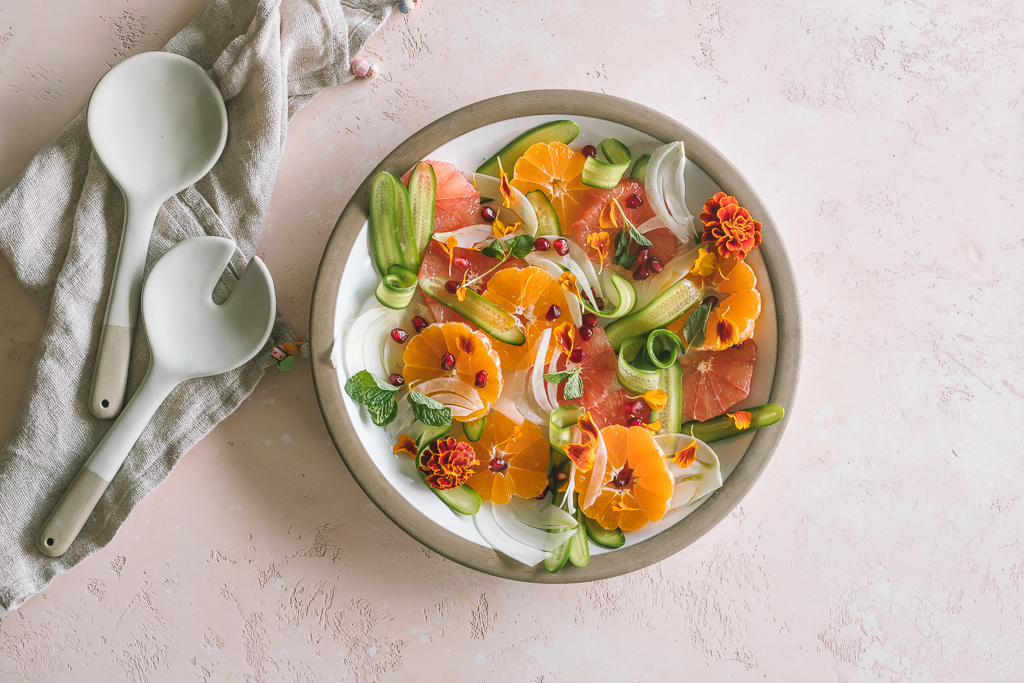 A citrus salad with shaved cucumber and fennel on a brown rimmed ceramic plate, ceramic salad servers and a linen tea towel